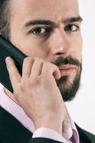 Close up portrait of young bearded businessman on the cellphone Stock Photography