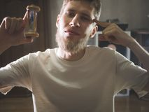 Close up portrait young bearded man student holding hourglass, time concept royalty free stock image