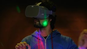Close-up portrait of young bearded man in vr glasses ticking air with finger. A close-up portrait young bearded man wearing virtual reality glasses ticking air stock footage
