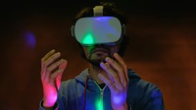 Close-up portrait of young bearded man in vr glasses ticking air with finger. A close-up portrait young bearded man wearing virtual reality glasses ticking air stock video footage