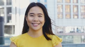 Candid smile of beautiful young asian female. Close-up portrait of young beautiful asian female looking at camera and smiling. Candid smile of attractive asian stock footage
