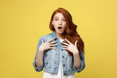Close up Portrait young beautiful attractive redhair girl shocking with something. Golden yellow Background. Copy space. stock image