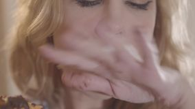 Close up portrait young beautiful blond woman greedily eating donut and licking her fingers. Young beautiful blond woman with long hair and red lipstick greedily stock video