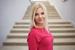Close up portrait of young beautiful blonde woman with trendy makeup in fuchsia blouse against concrete stairs background Stock Photos