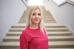 Close up portrait of young beautiful blonde woman with trendy makeup in fuchsia blouse against concrete stairs background Stock Image
