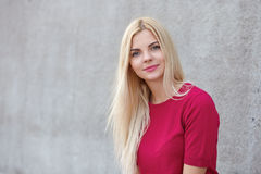 Close up portrait of young beautiful blonde woman with trendy makeup in fuchsia blouse against concrete wall blurred background Royalty Free Stock Photography