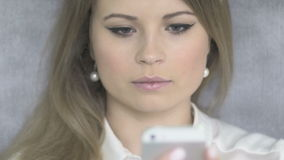 Close-Up Portrait of Young Beautiful Blonde Woman Using Phone. 4K stock footage