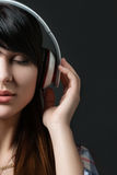 Close-up portrait of young beautiful brunette woman. Listening to music with her eyes closed and holding white headphones Stock Images