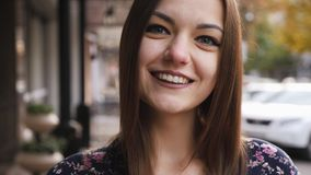 Close-up portrait of young beautiful businesswoman looking at camera, happy and smile on the street stock video