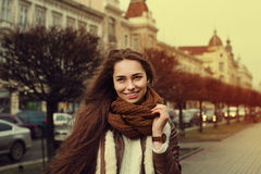 Close up portrait of young beautiful fashionable smiling girl wearing stylish clothes standing on the street. Old city Royalty Free Stock Photography