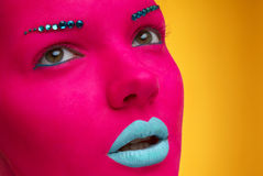 Beautiful girl with pink skin and blue lips on yellow Royalty Free Stock Photo