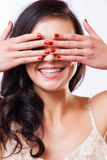 Close up portrait of young beautiful girl having fun and hiding her face with hand. Natural makeup and top knot hairdo Stock Photo