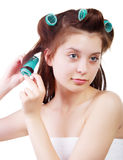 Close up portrait of Young beautiful girl having hair curlers on her head Royalty Free Stock Images