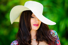 Close-up portrait young beautiful girl in a straw hat in the tro Royalty Free Stock Photo