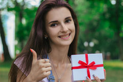 A close-up portrait of young beautiful girl who keeps a gift in hand, smiles. And shows class Stock Image