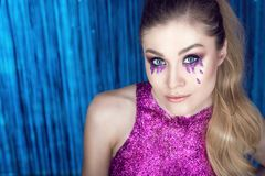 Beautiful glam model with artistic make up, glitter tears, wavy ponytail and top made of purple glitter. Close up portrait of a young beautiful glam model with Royalty Free Stock Photos