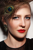 Close-up portrait of young beautiful glamorous woman with red li. Pstick and peacock feather royalty free stock photos