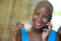 Close up portrait of young beautiful and happy black afro American business woman in trendy stylish hair talking on mobile phone d royalty free stock photo