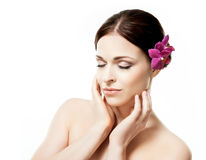 Close-up portrait of young, beautiful and healthy woman with an orchid Stock Photo