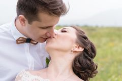 A couple of newlyweds standing in an arms embrace in nature Stock Photo