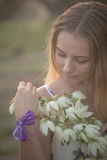 Close-up portrait.. Young beautiful pretty woman posing in long dress against in the field with white flowers Stock Photography