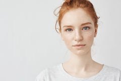 Close up portrait of young beautiful redhead girl in white shirt smiling looking at camera. Copy space. Isolated on Royalty Free Stock Photo