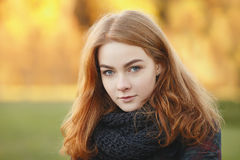 Close up portrait young beautiful redhead woman in scarf against blurred autumn foliage background cold season outdoors Royalty Free Stock Photography