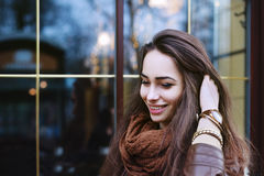 Close up portrait of young beautiful smiling woman wearing stylish clothes standing on the street. Model looking down Royalty Free Stock Image