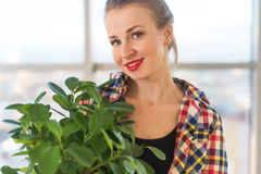 Close-up portrait of a young beautiful woman, holding decorative plant, smiling, looking at camera.  stock photo