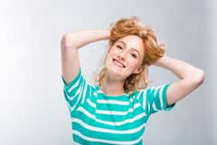 Close-up portrait of a young, beautiful woman with red curly hair in a summer dress with strips of blue in the studio on a gray ba royalty free stock photography