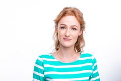 Close-up portrait of a young, beautiful woman with red curly hair in a summer dress with strips of blue in the studio on a gray ba Stock Photography