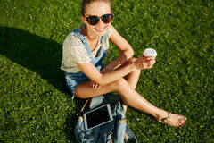 Close up portrait of young blonde girl with coffee and tablet Stock Image