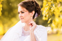 Close-up portrait of a young bride in autumn forest and leaves.  stock photo