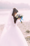 Close-up portrait of young bride in white dress and veil sniffing wedding bouquet with blue bow outdoors Royalty Free Stock Photography