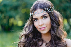 Close-up portrait of young brunette European type, with long curly hair and the decoration on the stock photography
