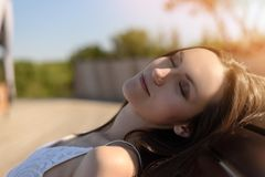 Close up portrait of a young brunette sleeping and breathing fresh air on sunbed stock images