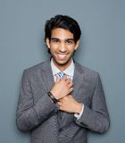 Close up portrait of a young business man smiling. Against gray background Stock Photo