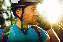 Close up portrait of young Caucasian cyclist in sportswear wearing helmet and blue t-shirt, talking on mobile phone with friend stock image