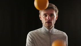 Close up portrait of young caucasian man juggling oranges stock video