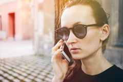 Close up portrait of young Caucasian woman in hipster sunglasses speaking on the phone. Beautiful female is talking on smart phoneon the street. Having mobile Royalty Free Stock Images