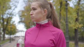 Close-up portrait of a young Caucasian woman in pink sportswear drinking water and running away. Confident female runner. Training in the autumn park in the stock video footage