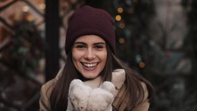 Close Up Portrait of Young Charming Girl Wearing Hat, Scarf, Mittens Blowing a Kiss and Smiling. Looking to Camera stock footage