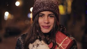 Close up portrait of young charming happy girl in winter hat and mittens, holding and hugging present box. woman