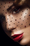 Close up portrait of young charming woman with brown eyes. Deep red lipstick and veil with black dots and red rubies. Black background Royalty Free Stock Photography