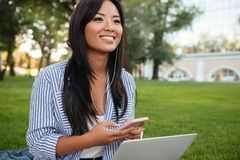 Close-up portrait of young cheerful asian woman, holding laptop, Royalty Free Stock Photography