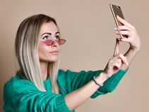 Close-up portrait of young cheerful fashion blonde woman in sweater wear makes selfie on smartphone, over beige background royalty free stock photo