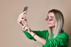 Close-up portrait of young cheerful fashion blonde woman in sweater wear makes selfie on smartphone, over beige background. Close-up portrait of young cheerful royalty free stock image