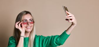 Close-up portrait of young cheerful fashion blonde woman in sweater wear makes selfie on smartphone, over beige background. Close-up portrait of young cheerful stock images