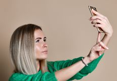 Close-up portrait of young cheerful fashion blonde woman in sweater wear makes selfie on smartphone, over beige background. Close-up portrait of young cheerful stock image