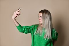 Close-up portrait of young cheerful fashion blonde woman in sweater wear makes selfie on smartphone, over beige background. stock images